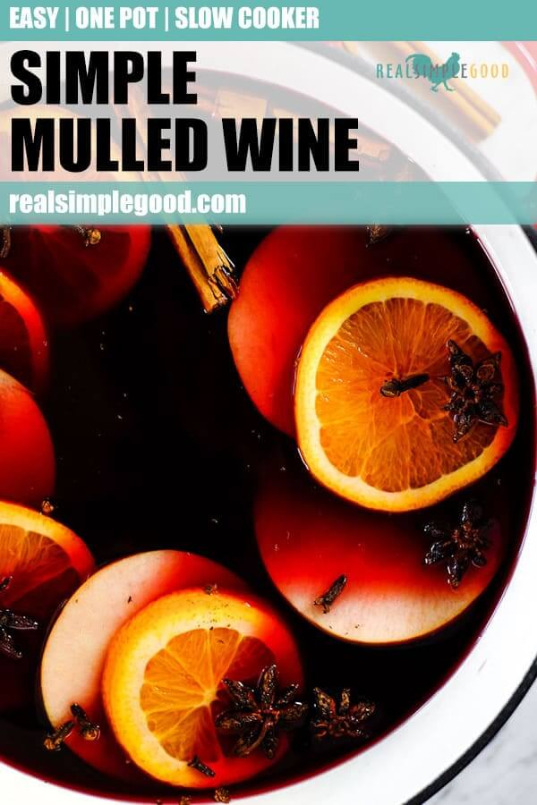 Simple mulled wine recipe in large dutch oven with slices of orange, apple, cloves, star anise and cinnamon sticks. Long pin for pinterest.