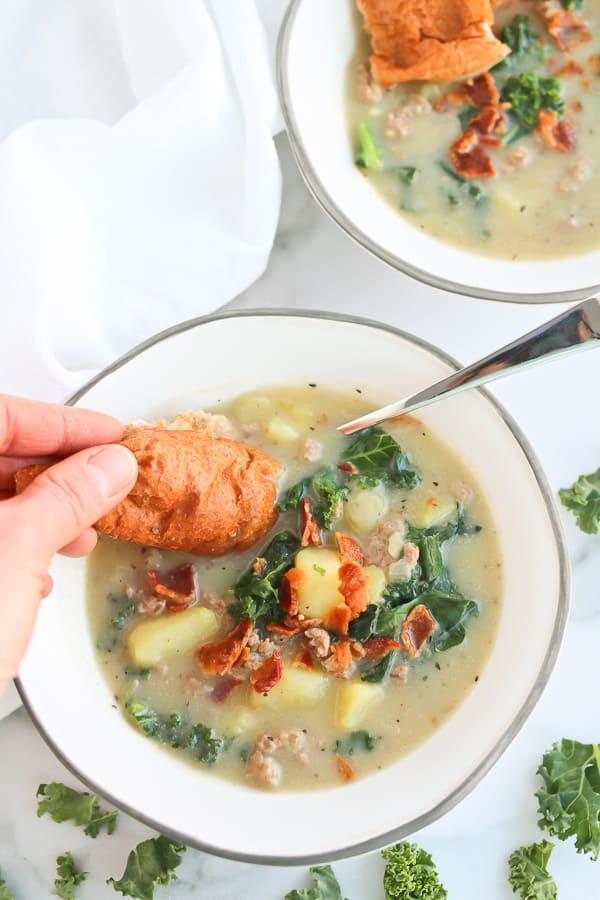 sausage, potato, kale soup in a white bowl