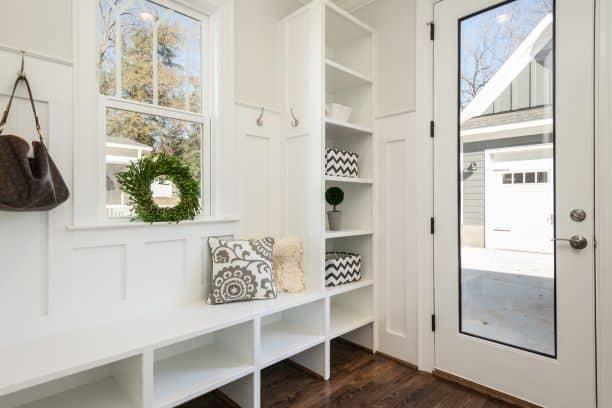 shoe bench under window near door with storage shelves,