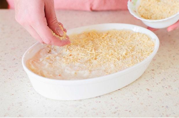 картофельное пюре в тарелке посыпают сыром