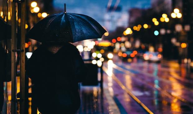 Pedestrian in black on a rainy night