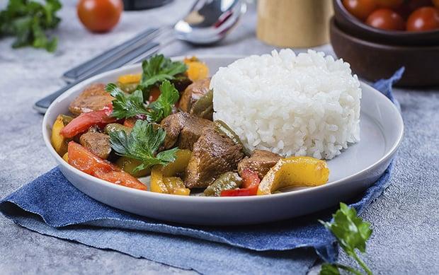 куриные грудки с овощами и вареным рисом на тарелке