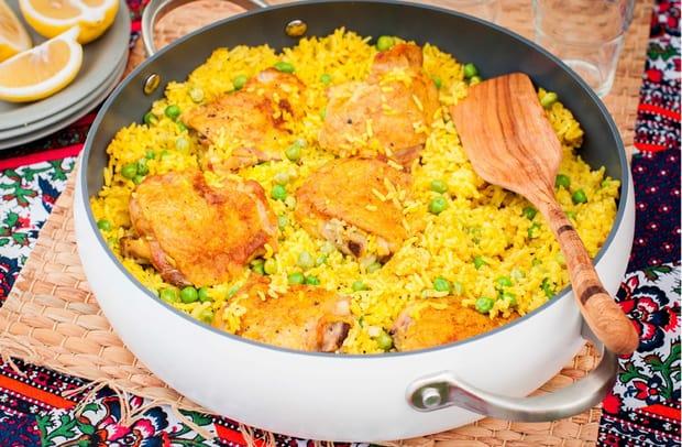 тушеные куриные бедрышки с рисом и зеленым горошкем с лопаткой в сковороде на столе, застеленном скатертью, рядом дольки лимона на блюдце