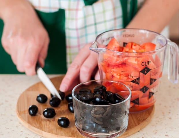 нарезанные помидоры в мерной чаше, маслины в пиале и на разделочной доске на столе