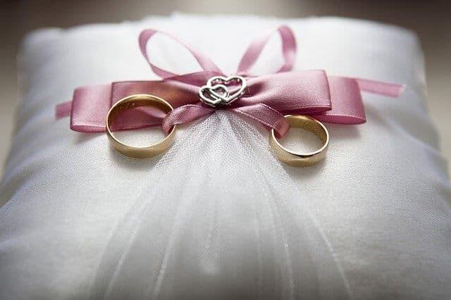 Akcesoria ślubne w postaci poduszki na złote obrączki z kokardką