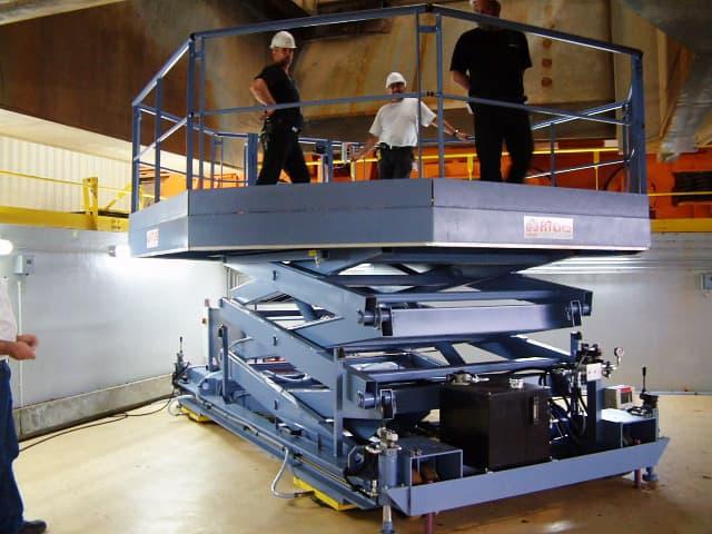Plateforme électro-hydraulique, à triple ciseaux superposés, mobile sur sol. Elle est tractable, équipée de stabilisateurs hydrauliques et de 4 coussins d'air afin de la positionner tout azimut.