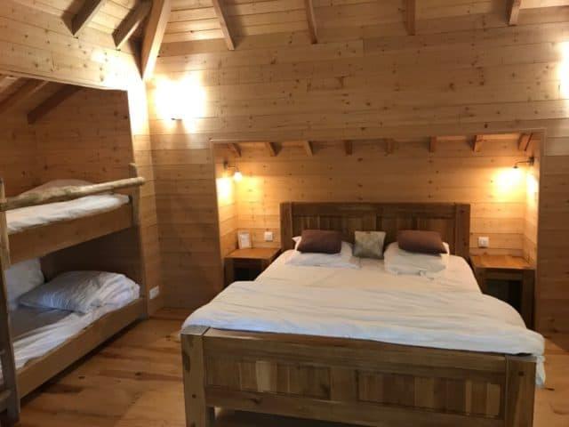 La chambre de la cabane Ecôtelia avec un grand lit et un lit superposé