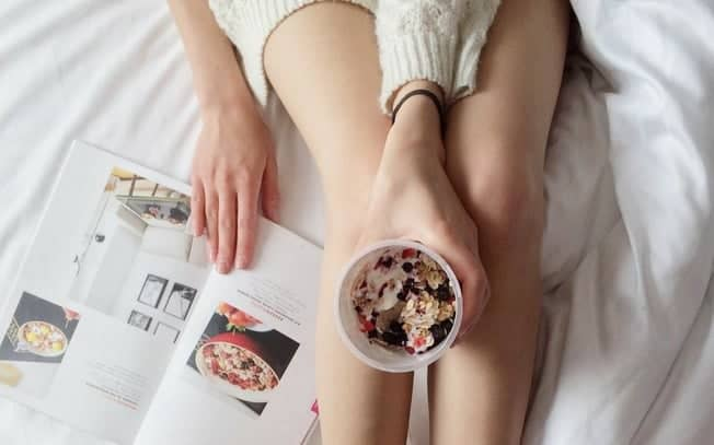 Person in bed reading a magazine and holding food