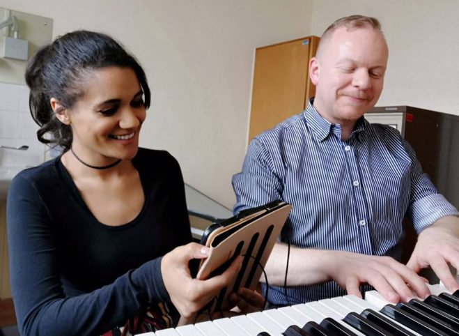 Nordoff Robbins music therapist and young woman playing piano