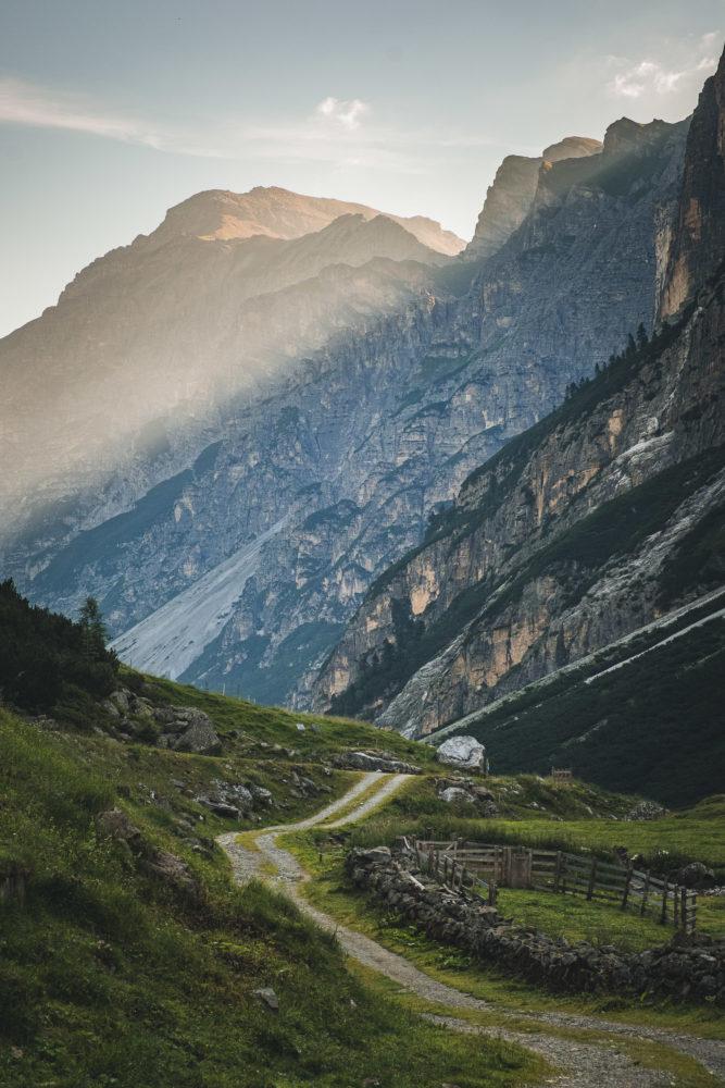 Wanderweg mit bewaldeten und kargen Felshängen