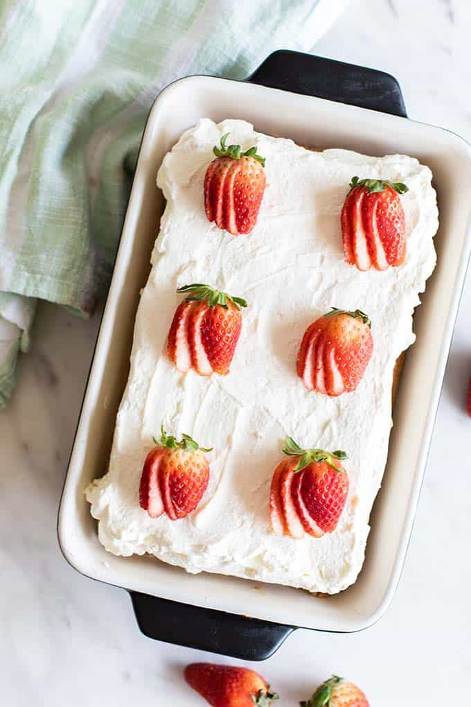 A top view of a whole tres leches cake topped with strawberries.