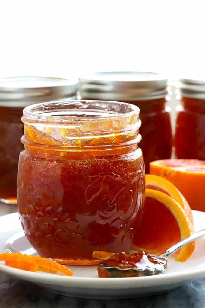 Jars of cara cara orange marmalade by a window