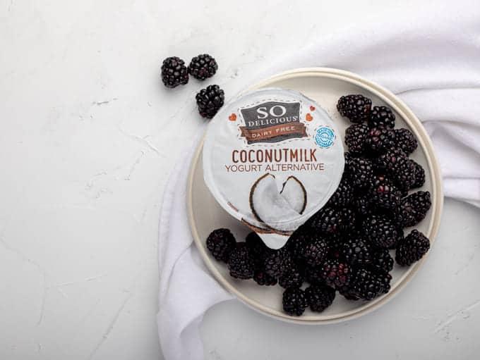Blackberries on white round plate with so delciious yogurt alternative