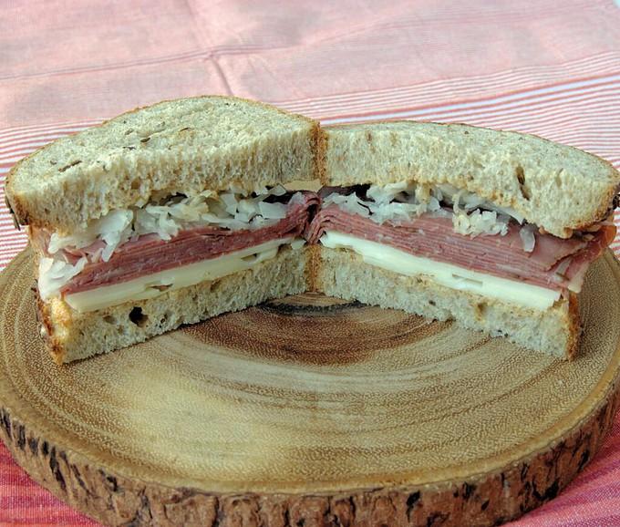 a reuben sandwich on a wooden tray