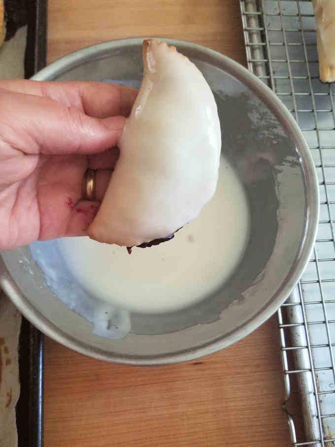 a hand pie freshly dipped in lemon glaze