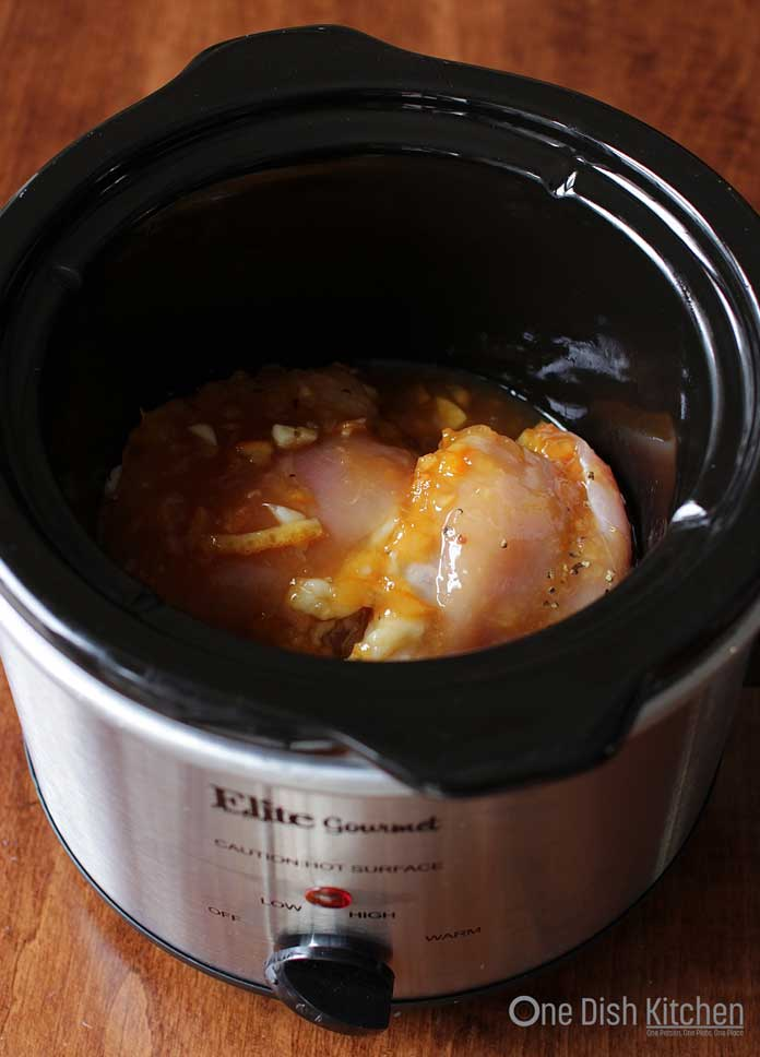 Chicken with orange sauce inside a small slow cooker