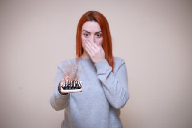 una donna guarda una spazzola piena di capelli