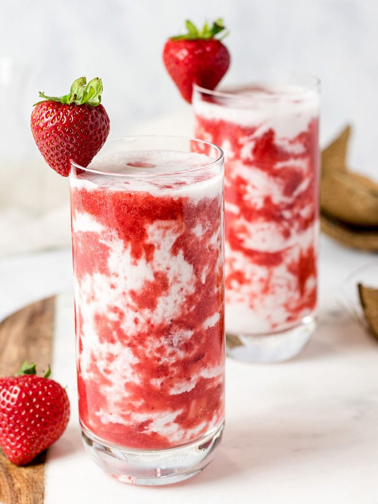 Tall glass with milk and strawberry puree.
