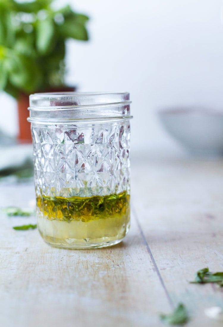 Pasta salad dressing in a glass jar.