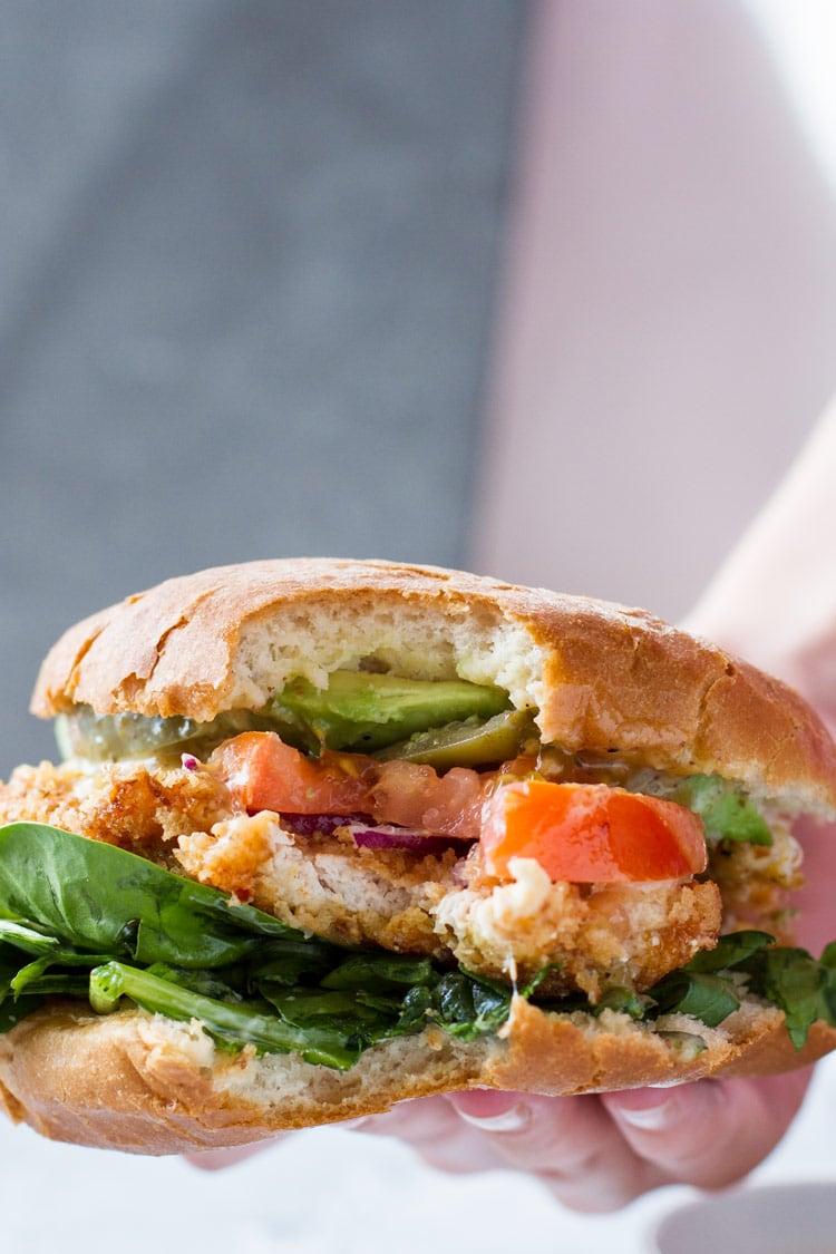 Closeup of a panko chicken burger that is taken a bite of.