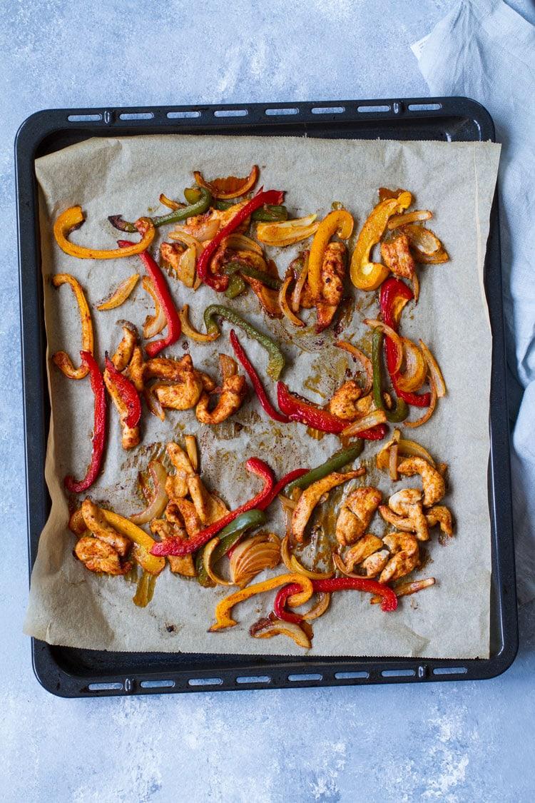 Chicken fajitas, baked, on a sheet pan. Blue background.