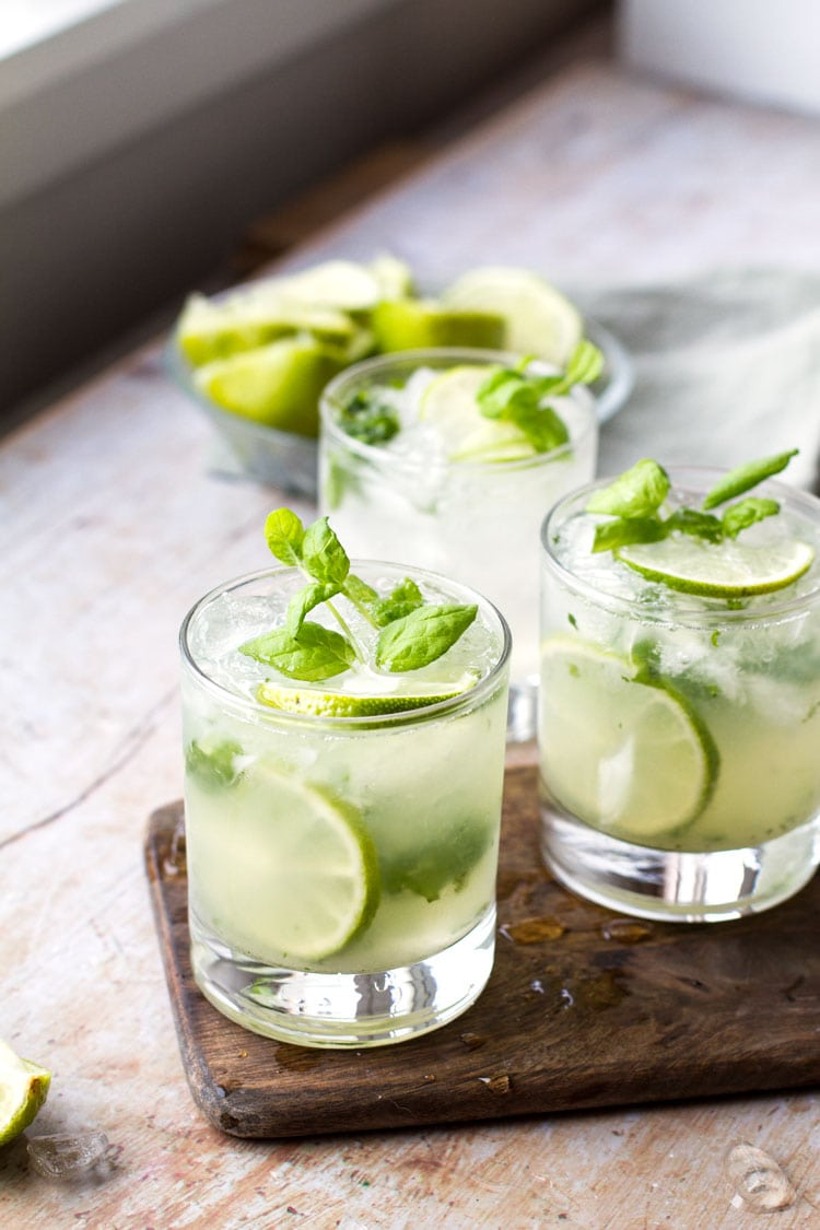 Three glasses with mojito, garnished with lime and fresh mint.
