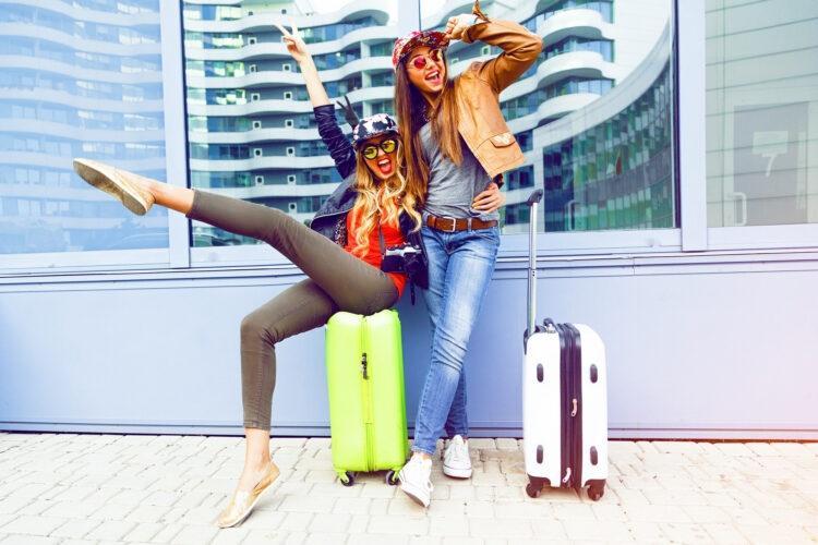 młode kobiety z walizkami cieszą się na lotnisku na wakacjach