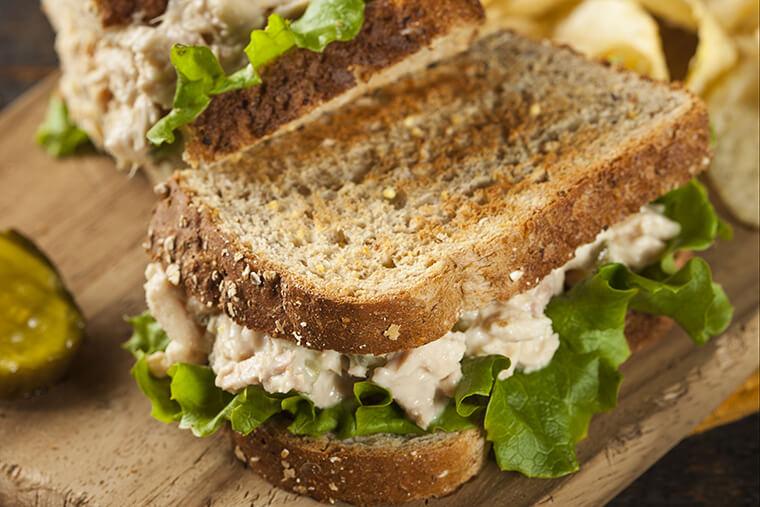 easy tuna salad sandwich on wood cutting board