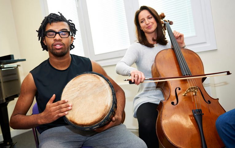 Nordoff Robbins music therapist and beneficiary with drum and cello
