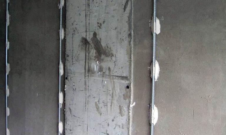 Установленные металлические маяки перед выравниванием стен