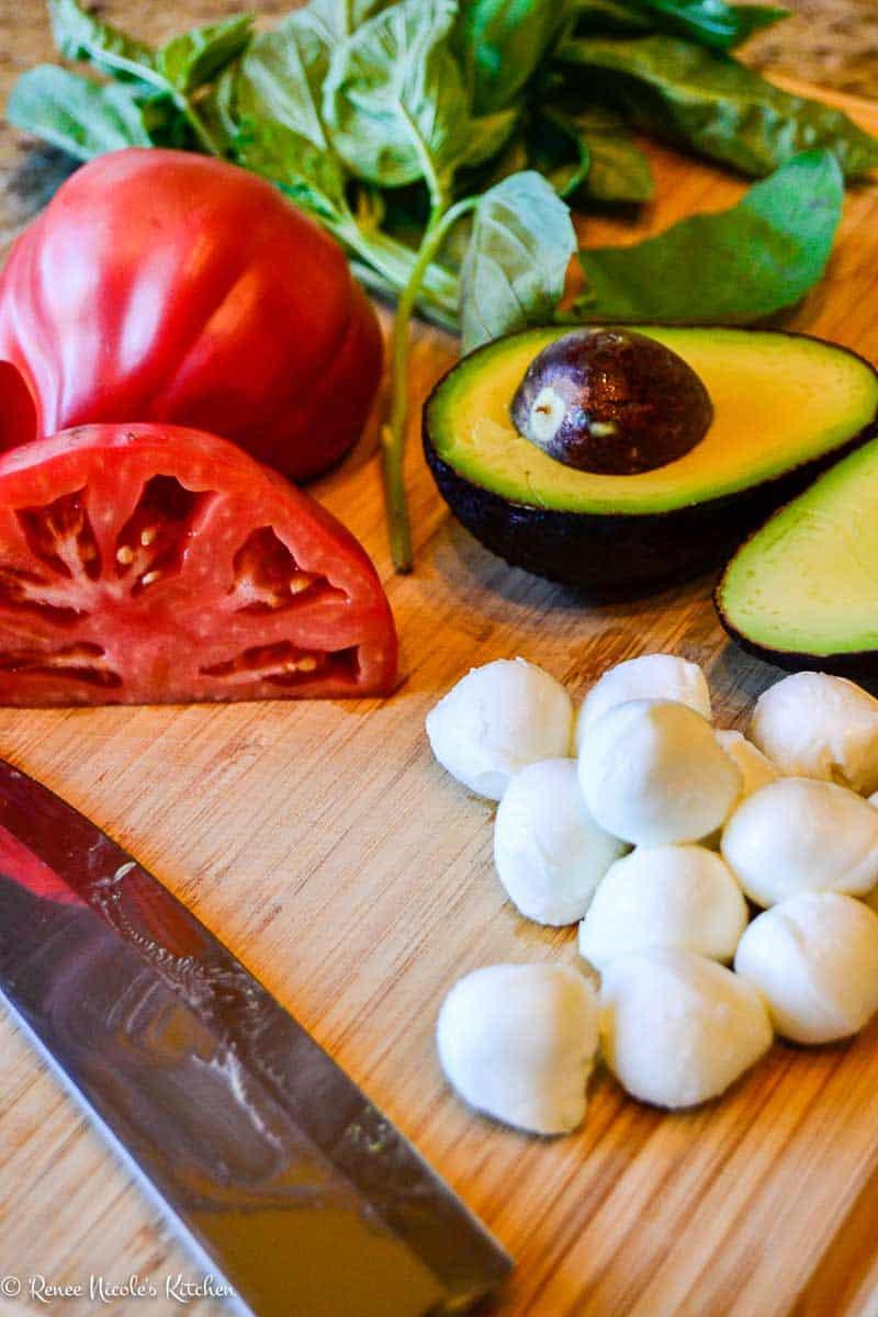 Loaded bruschetta toppings: tomato, basil, mozzarella, and avocado.