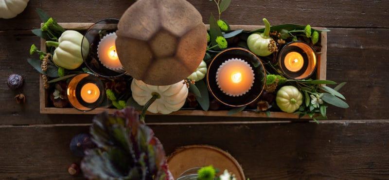 Tischdekoration mit Kerzen, Blumen und Kürbissen im Herbst