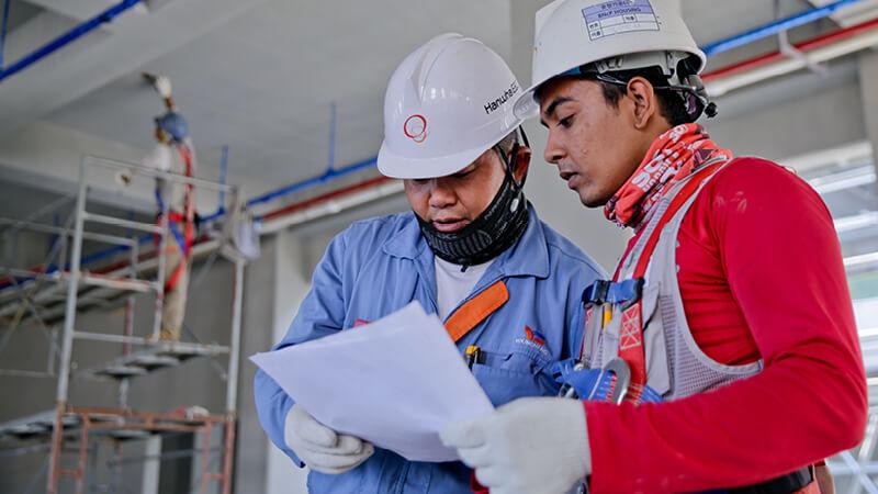 zwei Fabrikarbeiter besprechen sich