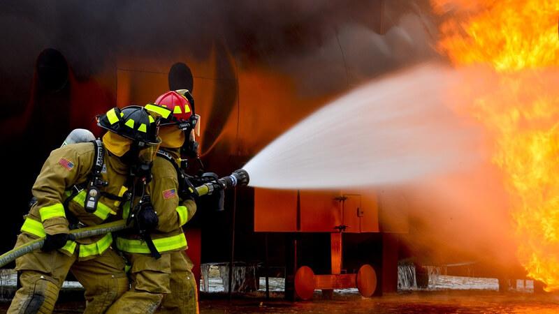 zwei Feuerwehrmitarbeiter löschen einen Brand