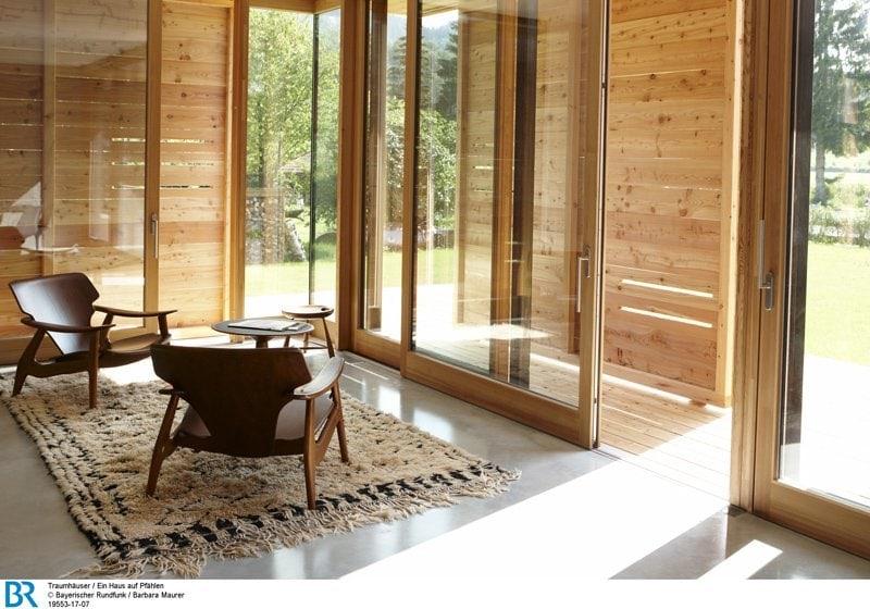 Raumhoch offen und über Eck verglast: der Wohnbereich mit halb geschlossenen Schiebeläden.