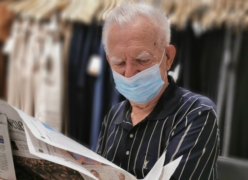 Old man reading paper wearing a disposable face mask