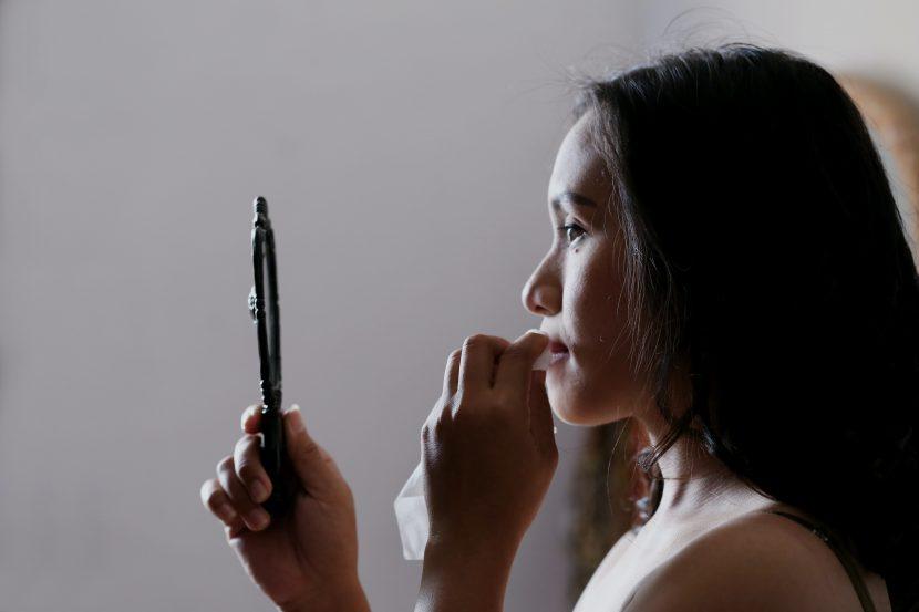 Sich selbst akzeptieren beim Blick in den Spiegel: Frau wischt sich die Lippen ab