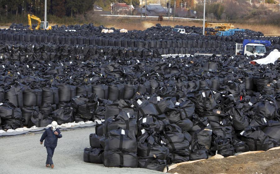 Un trabajador pasa junto a bolsas de basura radiactiva en un basurero temporal en Naraja, cerca de la planta nuclear de Fukushima Dai-ichi en Japón, el 5 de marzo de 2013. A dos años del temblor, un tsunami y un desastre nuclear que arrasaron con la costa noreste de Japón, la contaminación química sigue siendo una amenaza.