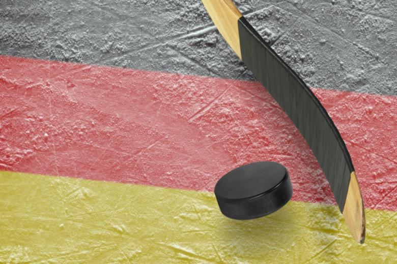 Хоккейная клюшка и шайба на фоне цветов немецкого флага фото
