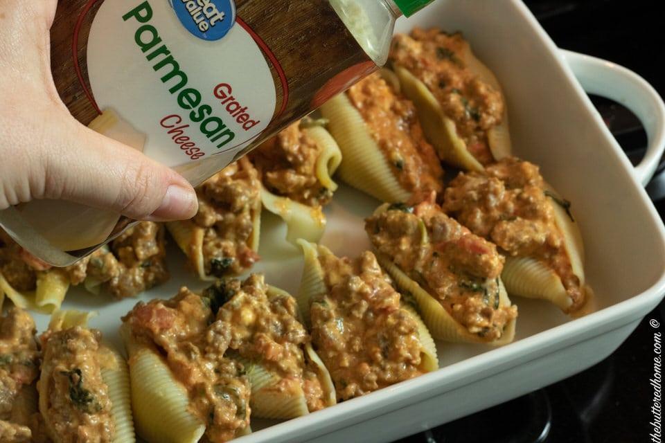 garnishing warm stuffed shells with grated parmesan cheese