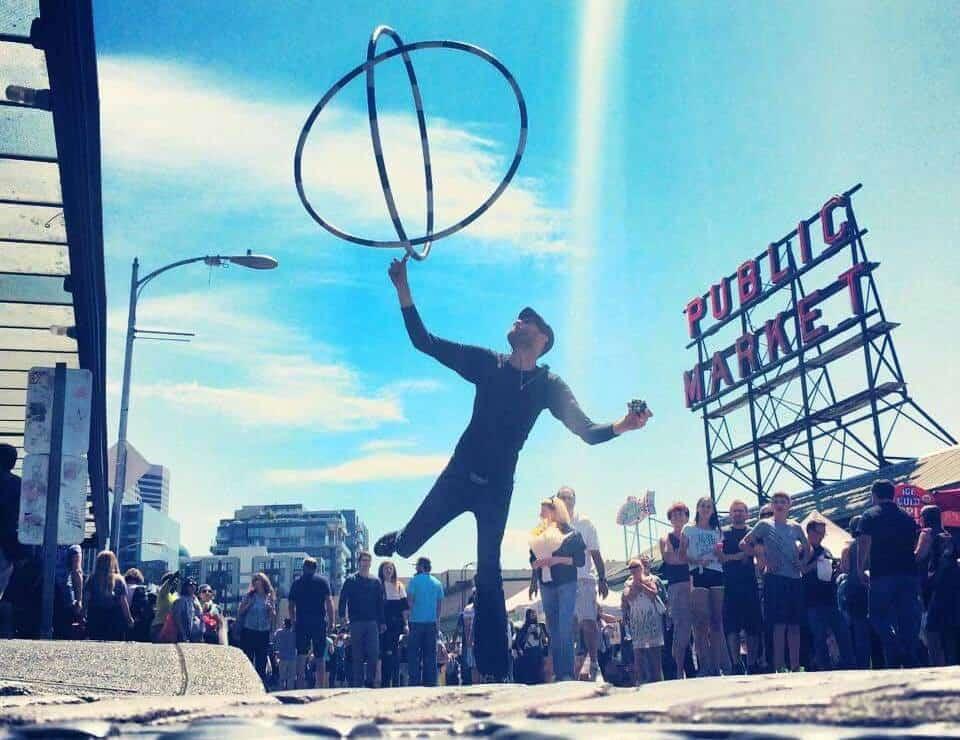 A busker juggles outside of pike place market in seattle