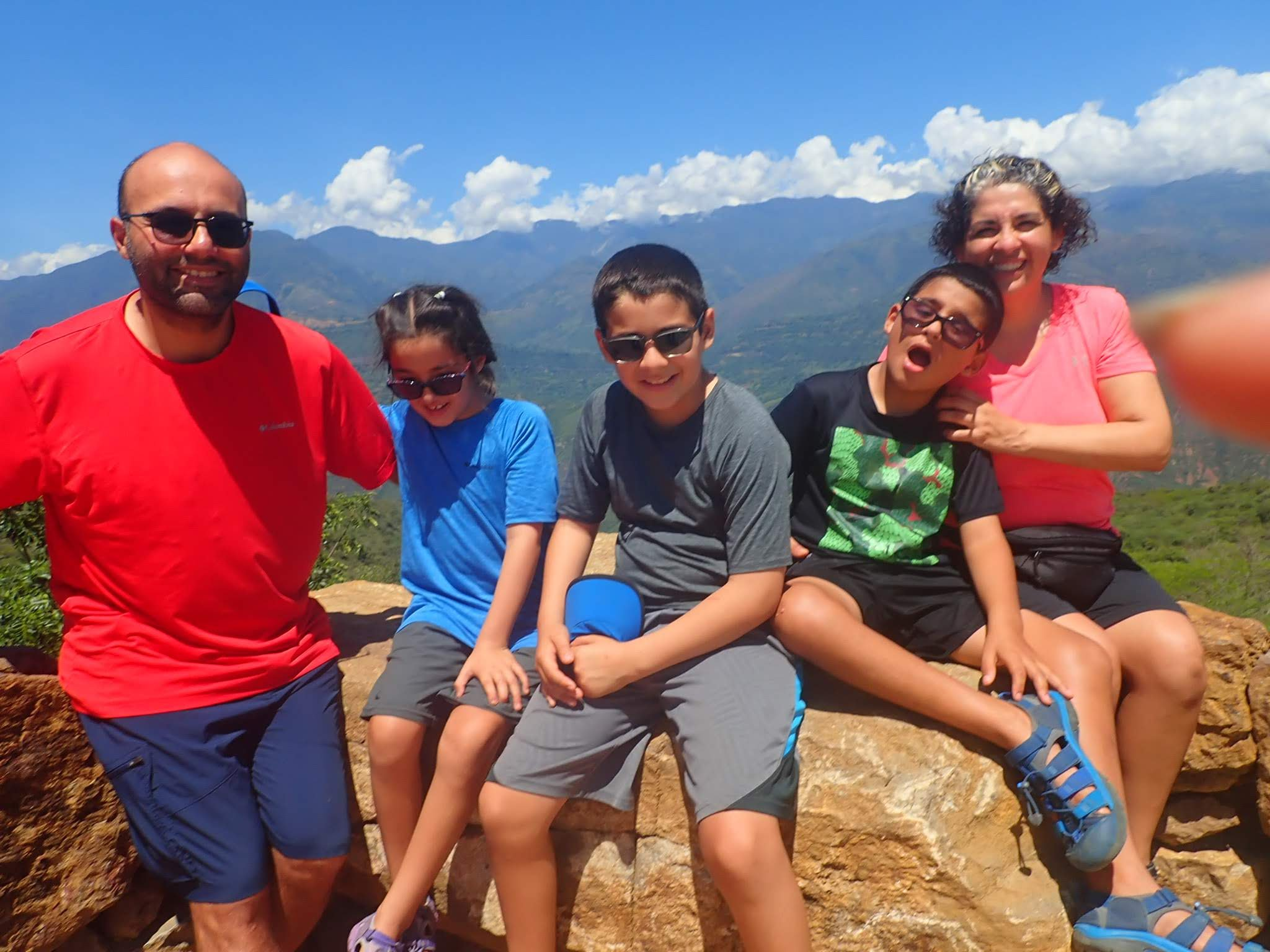 From left to right. Joe in a red shirt, Daniela in a blue shirt, Marco in a grey shirt, Mateo in the black shirt, and Charo in the pink shirt. We are sitting in Guane Colombia for this photo. The photographer's finger is also in the picture.