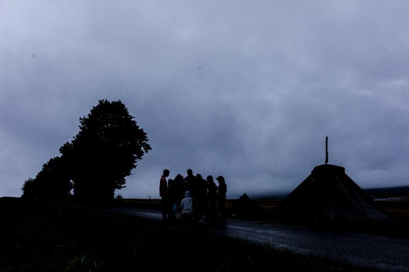 Ein Pfadfindergruppe steht am Ende einer Wanderung zusammen neben ihrem Zelt, der sogenannten Kothe, in der Dämmerung. / A scout group stands at the end of a hike together beside their tent, the so-called Kothe, in the twilight.