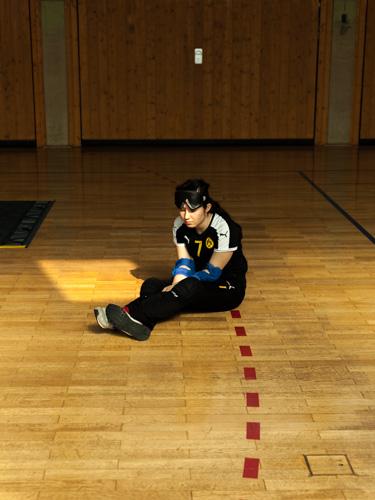 Eine Spielerin wartet sitzend auf dem Hallenboden auf ihre Einwechslung.