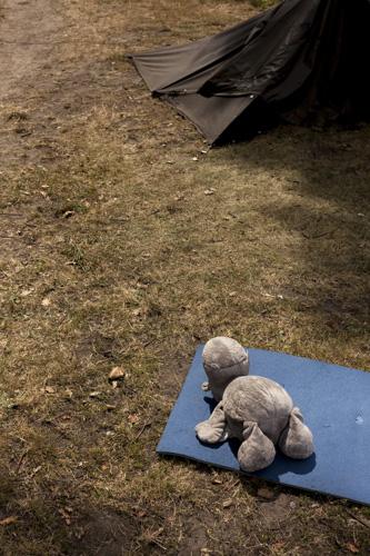 "Ein Stofftier liegt auf einer Isomatte vor einem Pfadfinderzelt, einer sog. ""Kröte"". in der Sonne. Für viele junge Pfadfinder ist ein Pfadfinderlager die erste Zeit in ihrem Leben, in dem sie längere Zeit von zu hause fort sind. / A stuffed animal lies on a mat in front of a scout tent, a so-called ""toad"". in the sun. For many young scouts, a scout camp is the first time in their lives when they are away from home for a long time."