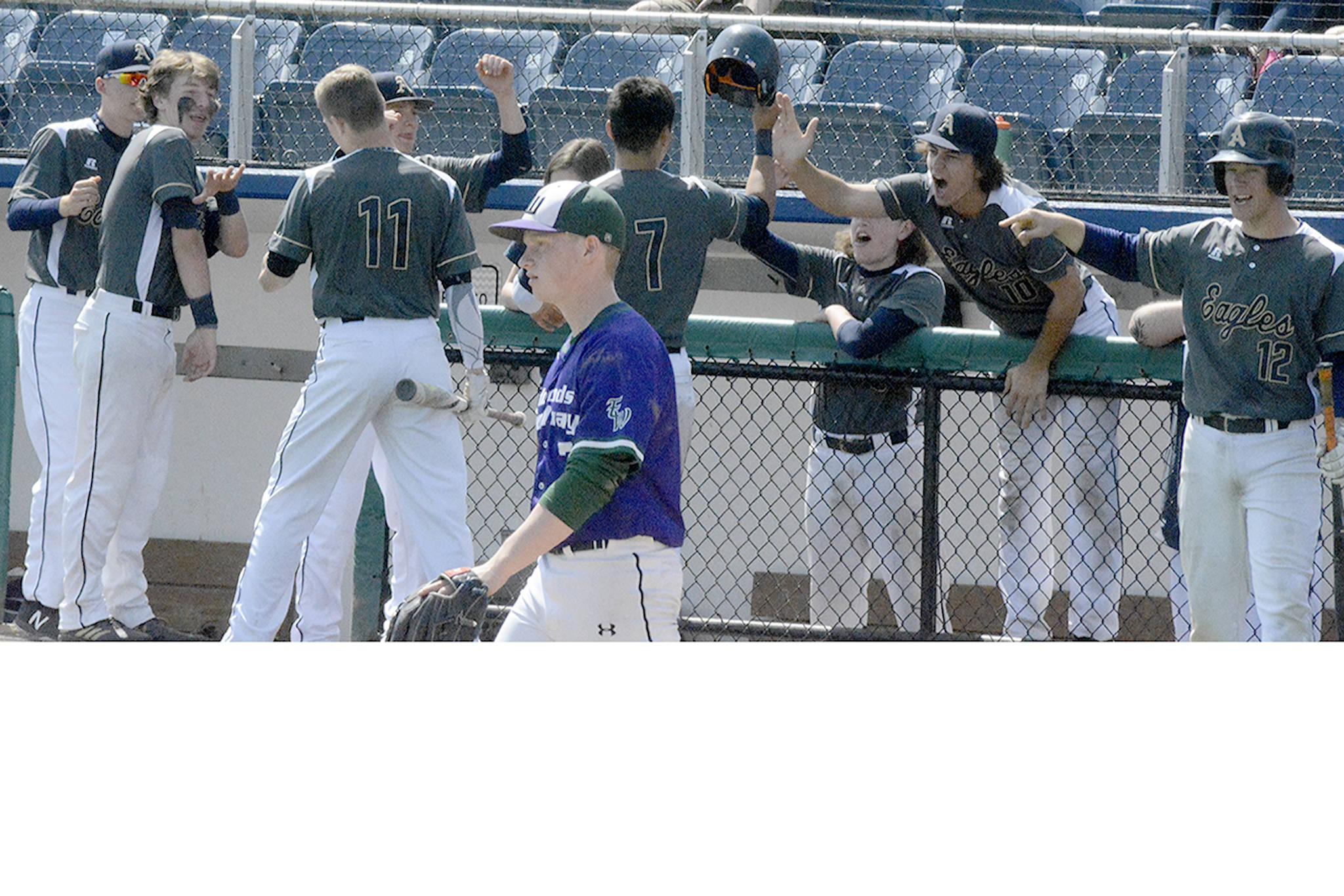 E-W's pitcher walks away as Arlington's boys baseball team celebrates their big inning.