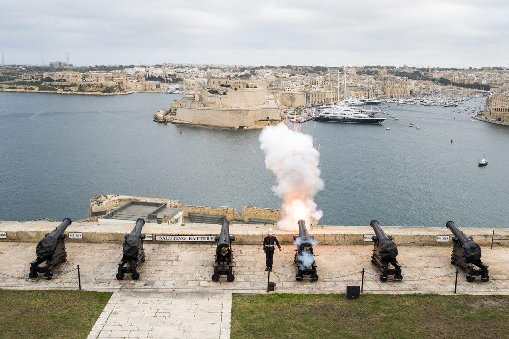 Fünf Kanonen stehen nebeneinander an einem Hafenbecken. Eine feuert einen Salut-Schuß ab.