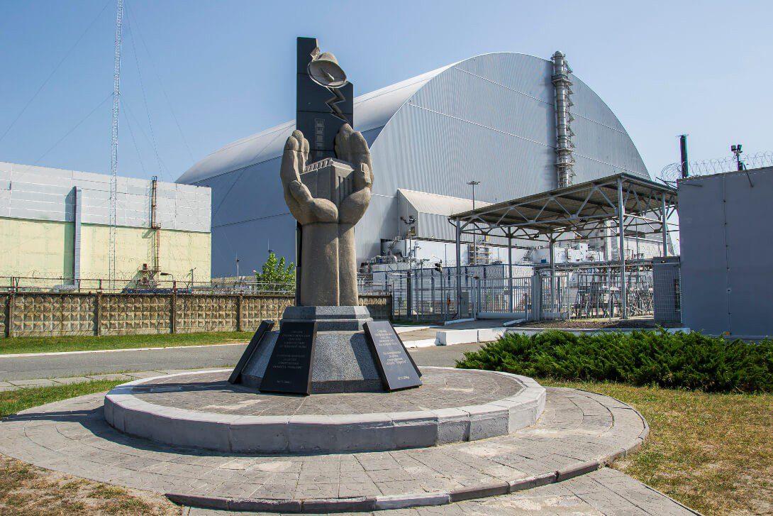Pomnik likwidatorów i sarkofar nad reaktorem nr 4 w Czarnobylu