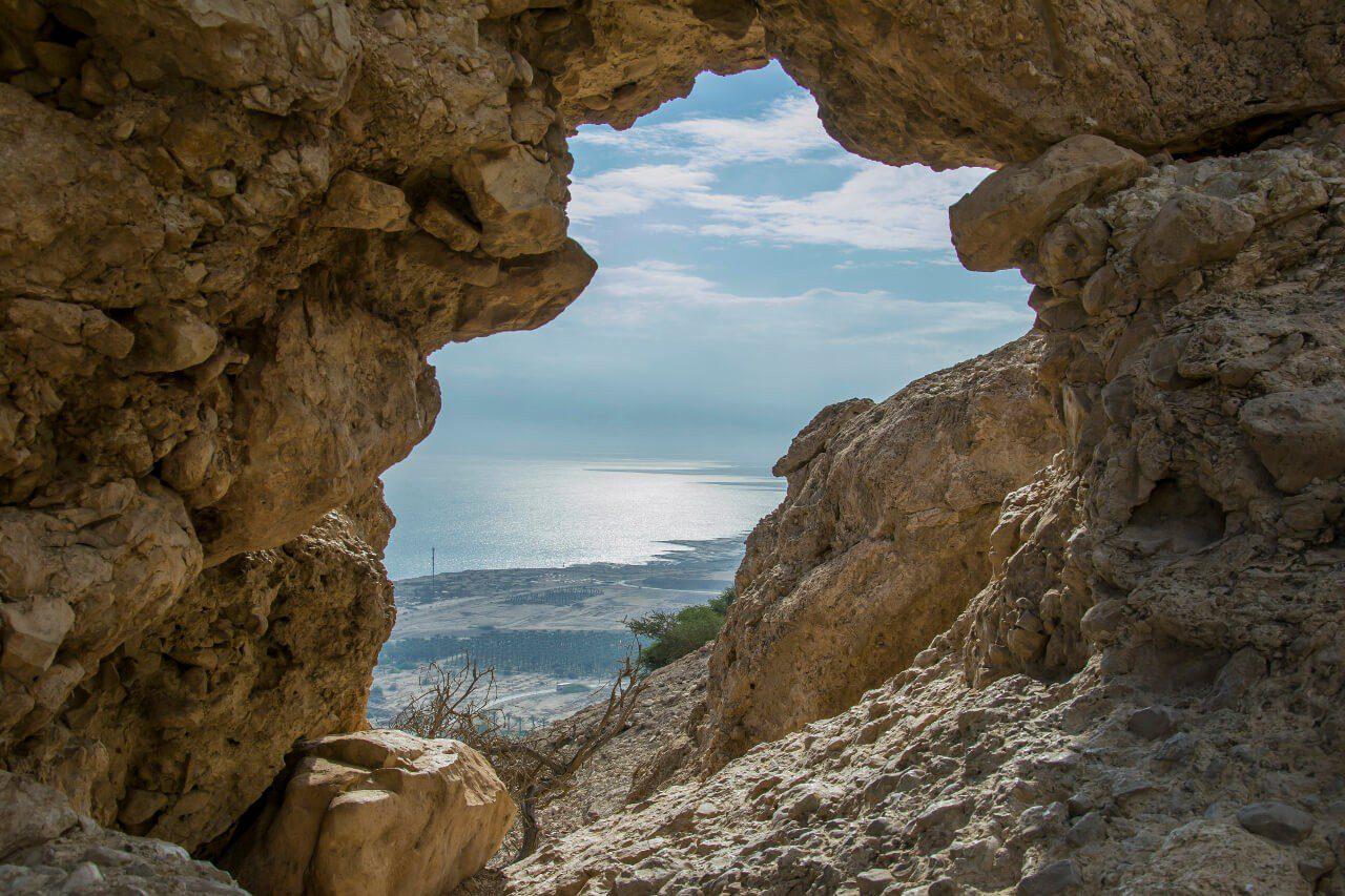 Widok na Morze Martwe przez szczelinę w skale.