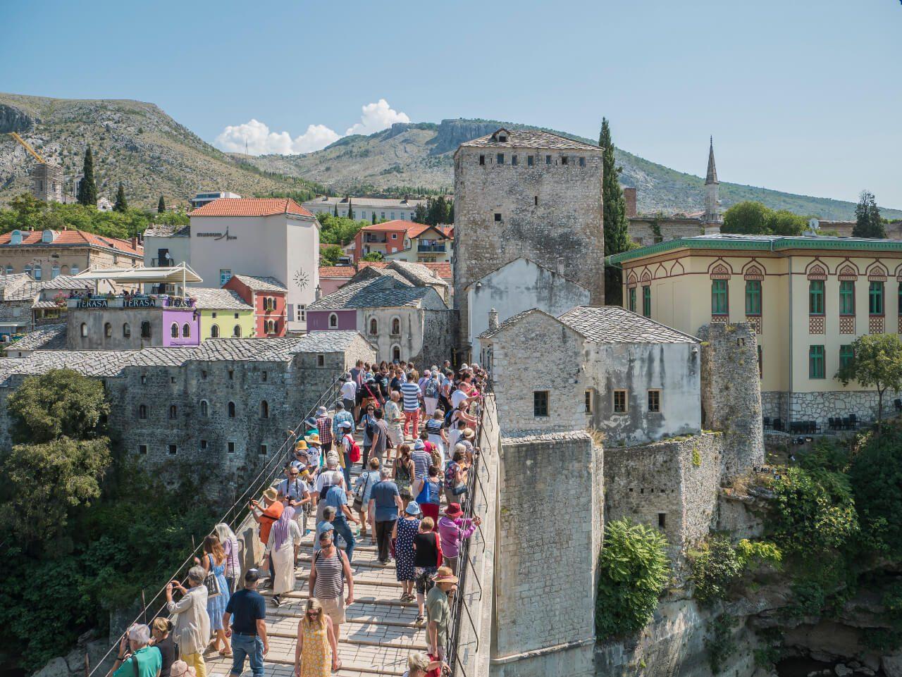 Tłumy przechodzące przez Stary Most, Mostar